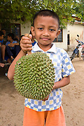 A young Orang Asli boy holds a durian fruit (Durio zibethinus) in Johore, Malaysia. Durian fruit is a popular and desirable fruit, but is associated with a foul and pungent odor.