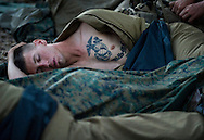 A tattooed Cody Harnish sleeps amongst his fellow Marines early one morning before the days' live-fire exercises for the 2nd Battalion, 5th Marine Regiment at Camp Pendleton.