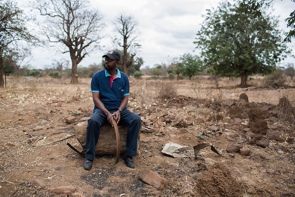 Chipanga, Tete province, Mozambique. Armando Saize stands by the remains of his house...Over 700 families from the villages of Chipanga, Mitete, Malabue-Gombe and Bagamoyo were resettled to Cateme village, a Vale resettlement compound. Vale deliberately divided the communities in two with employed villagers moving to 25 de Setembro since it is closer to Moatize and the coal mine. The unemployed were resettled to Cateme, 40 km from the original town. While the most immediate problem of the community is the enormous distance to Moatize, their old habitat, they also suffer from unproductive farmland which can only be reached via a two hour walk, no access to markets and infrastructure and poorly constructed houses not fitted to the people's needs with temperatures inside reaching as high as 65° C due to the construction with tin clad roofs and missing isolation.