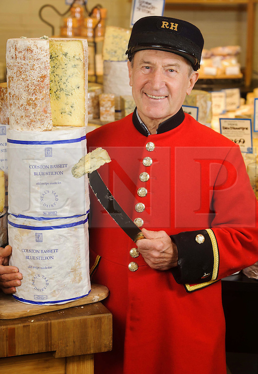 """© Licensed to London News Pictures. 17/12/2013 London, UK. Chelsea Pensioner Jimmy Anderson celebrates the 100th anniversary of Colston Bassett Stilton at Whole Foods Market, Kensington, London. The world renowned cheese has been made in the same Nottinghamshire factory  since 1913 where only 4 head cheese makers have overseen the process. The cheese won  """"Best British Cheese' at this years World Cheese Awards.<br /> Photo credit : Simon Jacobs/LNP"""