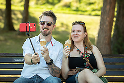 © Licensed to London News Pictures . 13/09/2019. Bournemouth, UK. A couple take a selfie as they eat ice creams in Bournemouth Central Park as a late summer heatwave brings high temperatures to the south coast of England . Photo credit: Joel Goodman/LNP