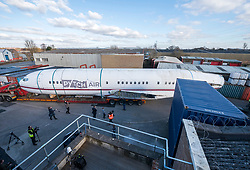 © Licensed to London News Pictures; 27/02/2021; Bristol, UK. A Boeing 727 fuselage is manoeuvred into the yard of the business Pytch in Brislington having been transported by road from Cotswold Airport to Bristol via the M5 and M4. Pytch owner Johnny Palmer will use the plane fuselage for an eco-friendly office and event space for the business. The plane as used by Japan Airlines before going into private ownership in the 1970s, sold for £50million when new. Mr Palmer got it for less than £100,000 because it does not have an engine or wings. Photo credit: Simon Chapman/LNP.