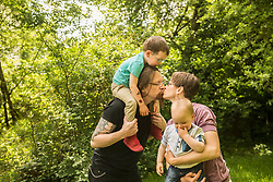 Little boys with parents kissing at the garden