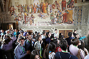 mass of tourists inside the Vatican Museum in room with painting School of Athens by Raphael