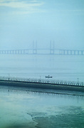 SUNRISE SEA, Malaysia. Suspension bridge. Early morning mist. Fishing boat, suspension bridge joining Penang to the mainland, between Georgetown and Butterworth.