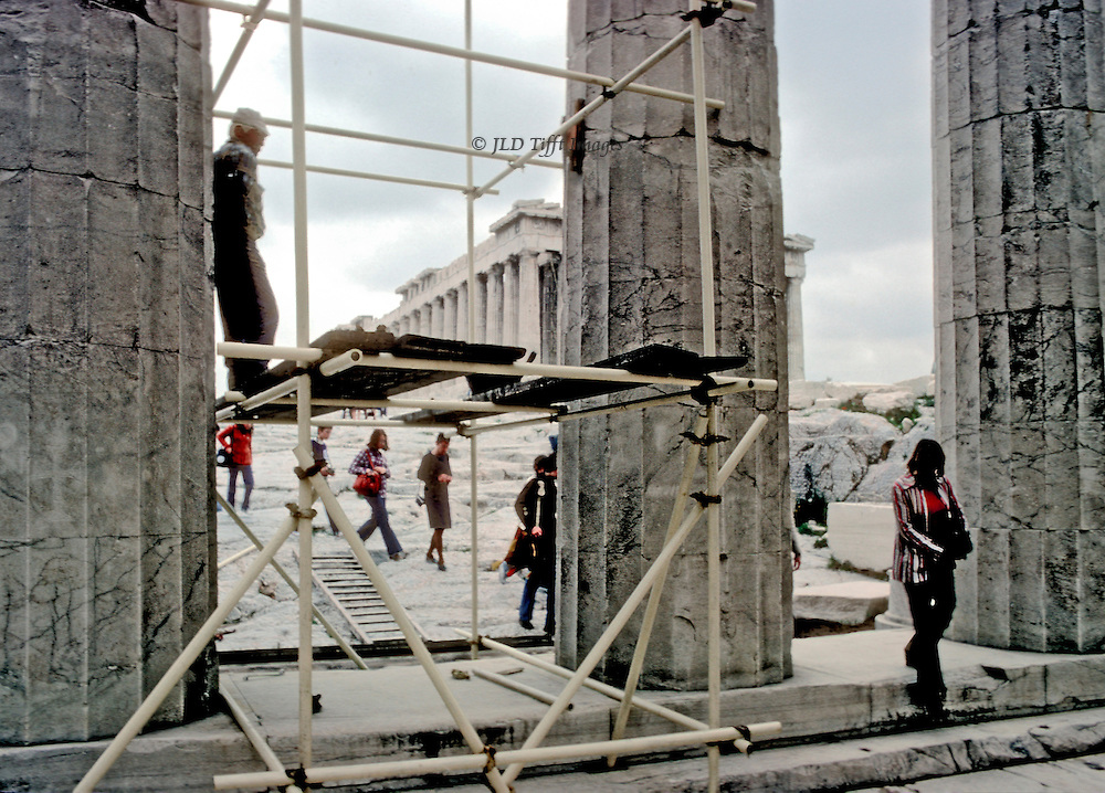 Athens Acropolis Propylaea with scaffolding preparatory to restoration program in 1978.  One workman stands on a platform, leaning against a column, watching as a line of tourists, mostly women, exits the Acropolis site through the Propylaea columns.