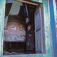 An elderly Sherpa woman turns a huge prayer wheel at a small temple in Namche Bazaar, the leading town for the  Sherpa culture in Nepal.