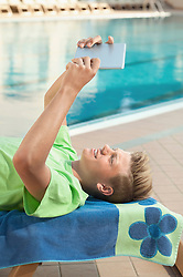 Boy swimming pool holding tablet computer holiday