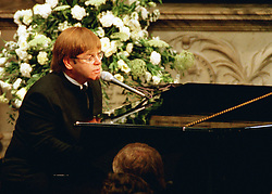 Singer Elton John performing a rewritten version of his song 'Candle in the wind' as a tribute to Diana, Princess of Wales, at her funeral. Over a million mourners lined the route of the funeral procession through London.