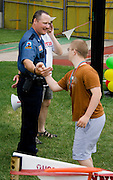 Policeman congratulating champion with medals around neck. Special Olympics U of M Bierman Complex. Minneapolis Minnesota USA