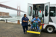 """Nofomuli Finaulahi helps Bruce Oka out of the San Francisco Paratransit Bus the """"Grayce Reagan"""" at Fort Point in front of the Golden Gate Bridge"""