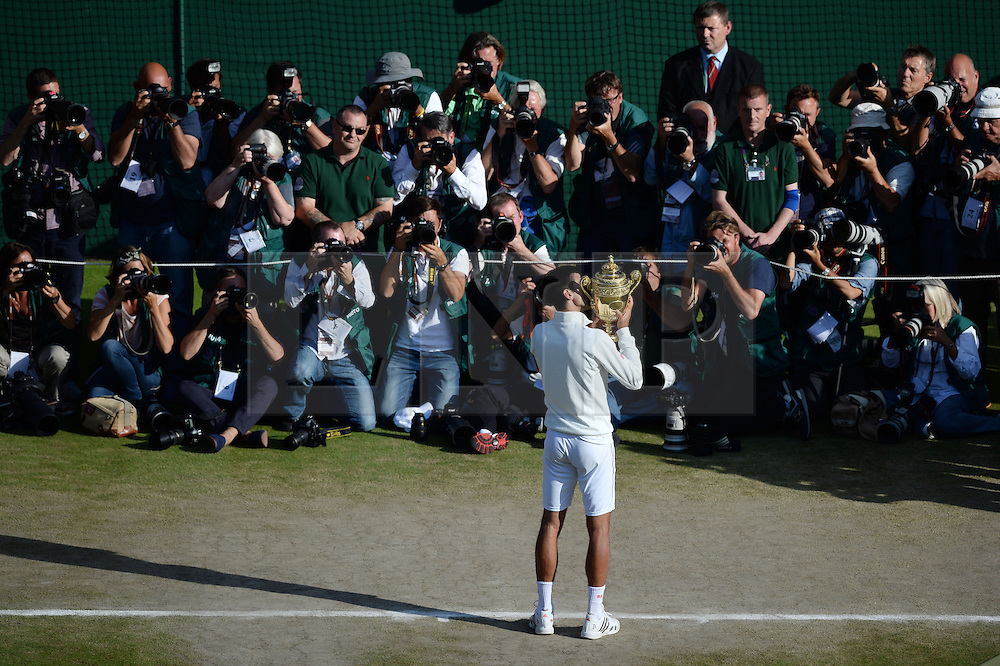 © Licensed to London News Pictures. 6th July 2014. London. UK. Djokovic receives winners trophy. Crowds and celebrities watch the The Men's Final between Roger Federer, SUI v Novak Djokovic, SER at the Wimbledon Tennis Championships 2014. Photo credit : Mike King/LNP