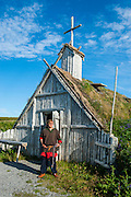 Traditional dressed man before a viking church in the Norstead Viking Village and Port of Trade reconstruction of a Viking Age settlement, Newfoundland, Canada