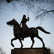Bare branches frame the silhouette of a large statue of Venezuelan leader Simon Bolivar, by Felix de Weldon, that stands in a park in front of the Interior Department in Foggy Bottom in northwest Washington DC. The statue was installed as a gift of the Venezuelan Government in 1955 and is formally titled Equestrian of Simon Bolivar.