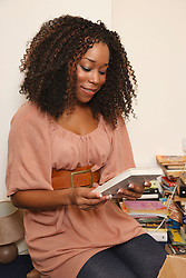 Young black woman unpacking books..