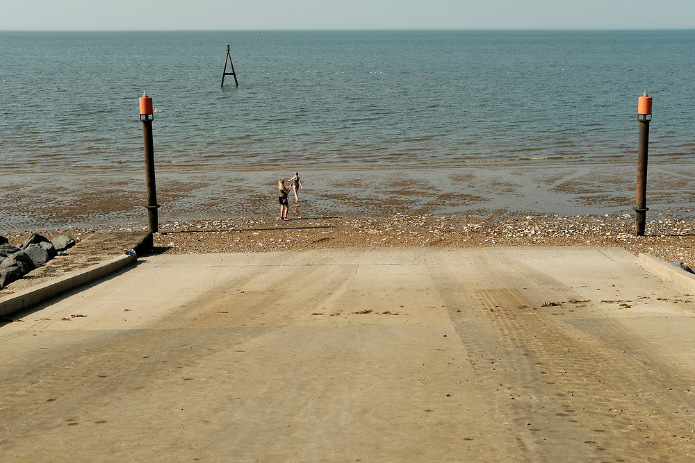 Concrete slip way ramp leading down to the beach where children are playing in the summer sunshine. Taken on the last hot day of the Summer in Hunstanton Norfolk, the first summer in the UK during the COVID-19 pandemic.<br /> <br /> Photo by Jonathan J Fussell, COPYRIGHT 2020