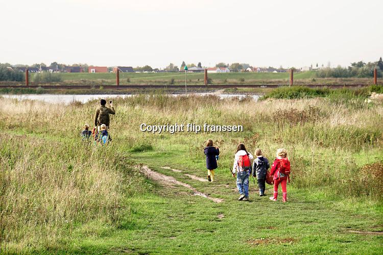Nederland, Ooijpolder, 13-10-2020 Kinderen wandelen met een volwassen begeleider langs de rivier in de Gelderse Poort bij de Vlietberg . Het is buitenschoolse opvang, bso,  van de stichting struin die jonge mensen natuureducatie geeft .Foto: ANP/ Hollandse Hoogte/ Flip Franssen