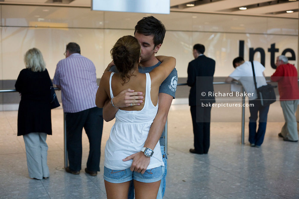 "Amid the hectic arrivals concourse of Heathrow airport's Terminal 5, a young couple kiss and hold on to each other after a few weeks separation when the girl took a family holiday away from her boyfriend who needed to work here in London. They have clearly missed each other after such a short break from each other but are otherwise oblivious to the crowds that surround them in this busy international airport. The boy holds the girl's bottom in a display of sexuality that is frowned upon in other cultures where open sexual behaviour is taboo. From writer Alain de Botton's book project ""A Week at the Airport: A Heathrow Diary"" (2009)."