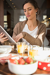 Mid adult woman using a digital table at breakfast table, Munich, Bavaria, Germany