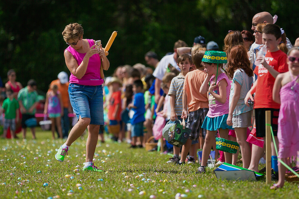A parent treads carefully to snap a cell phone photo of participants before the 21st annual Royal Scoop Easter Egg Hunt at New Life Church on Saturday, April 4, 2015, in Bonita Springs.  The annual Easter event featured a 25,000-egg Easter egg hunt, relay races and an ice cream eating contest.