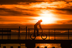 © London News Pictures. 06/05/2018. Aberystwyth, UK. A the end of a warm and sunny May Bank holiday Sunday, people on the jetty in Aberystwyth are silhouetted against the spectacular setting sun as they walk and cycle. Photo credit: Keith Morris/LNP