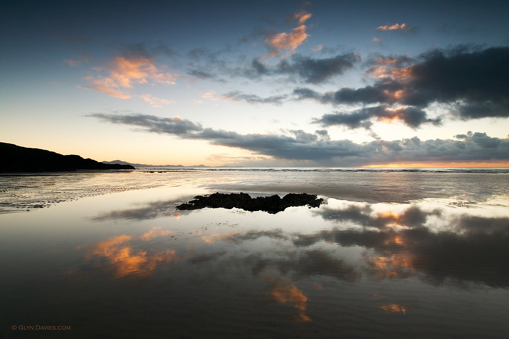 Sunset reflected in a large sand pool on this expansive West Anglesey beach at Aberffraw
