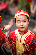 """10 FEBRUARY 2013 - BANGKOK, THAILAND:   A boy dressed as a Chinese Mandarin during Chinese New Year on Yaowarat Road in Chinatown in Bangkok. Bangkok has a large Chinese emigrant population, most of whom settled in Thailand in the 18th and 19th centuries. Chinese, or Lunar, New Year is celebrated with fireworks and parades in Chinese communities throughout Thailand. The coming year will be the """"Year of the Snake"""" in the Chinese zodiac.  PHOTO BY JACK KURTZ"""