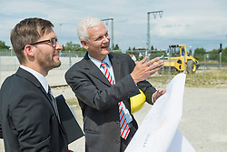 Two businessmen with construction plan on construction site