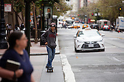 Een jongen rijdt op een skateboard over Market Street in San Francisco. De Amerikaanse stad San Francisco aan de westkust is een van de grootste steden in Amerika en kenmerkt zich door de steile heuvels in de stad.<br /> <br /> A boy is riding a skateboard at the Market Street in San Francisco. The US city of San Francisco on the west coast is one of the largest cities in America and is characterized by the steep hills in the city.