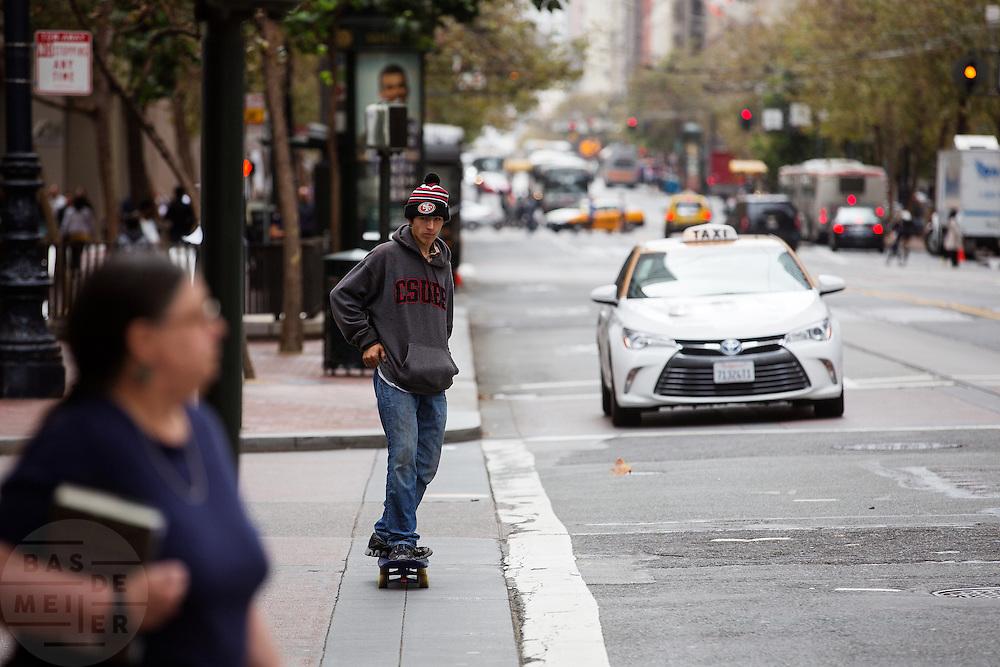 Een jongen rijdt op een skateboard over Market Street in San Francisco. De Amerikaanse stad San Francisco aan de westkust is een van de grootste steden in Amerika en kenmerkt zich door de steile heuvels in de stad.<br /> <br /> A boy is riding a skateboard at the Market Street in San Francisco. The US city of San Francisco on the west coast is one of the largest cities in America and is characterized by the steep hills in the city.