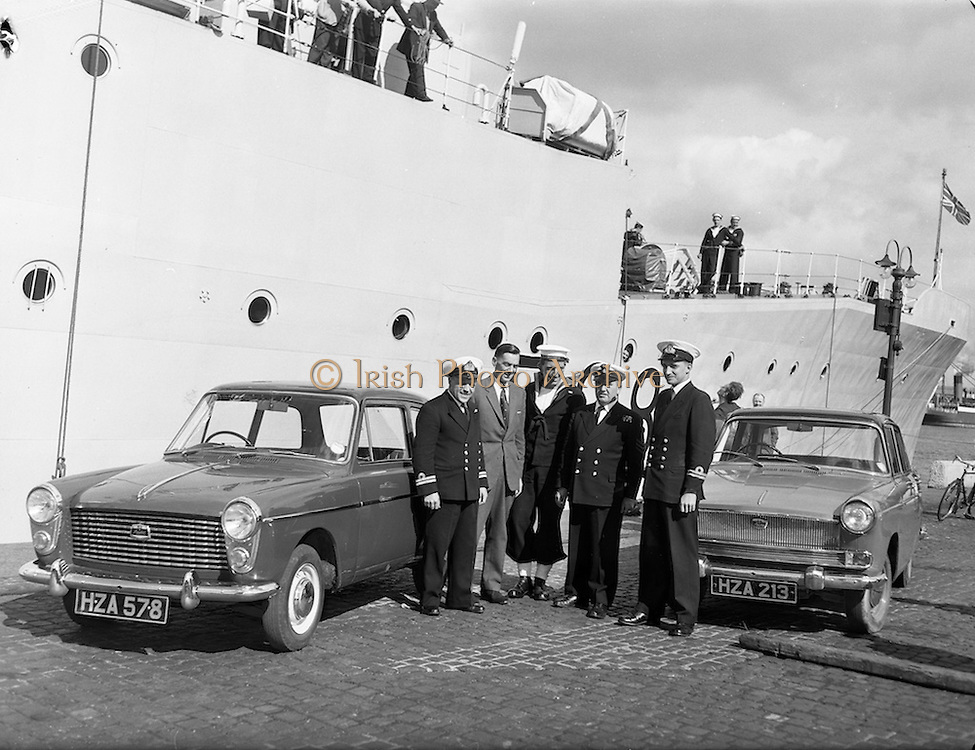 """07/09/1960<br /> 09/07/1960<br /> 07 September 1960<br /> British Navy vessel """"Malcolm"""" in Dublin.<br /> The British Navy fishery protection vessel Malcolm (1,500 tons) flaship of the R.N. Protection Squadron commanded by Captain H.H. Bracken arrived for a five day visit in Dublin Lincln and Nolan of Dublin supplied two Austin cars for the use of the officers during their stay and handed over the keys to the navy men on arrival. Picture shows officers and men of the H.M.S. Malcolm chatting to Mr. jack O'Donoghue, P.R.O. Lincoln and Nolan at the South Wall, Dublin, where he handed over the two Austin cars. L-R are Lieutenant Worth R.N.; Mr O'Donoghue; Leading Seaman Coles; Petty Officer Scott and Lieutenant James Royal Australian Navy."""