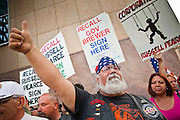 15 APRIL 2011 - PHOENIX, AZ: A member of the Tea Party tries to block immigrants' rights supporters at a Tea Party rally in Phoenix, AZ, Friday. About 500 supporters of the Tea Party movement rallied Friday at the Arizona State Capitol to mark tax day. They protested high taxes, the federal deficit, the debt limit and immigration policy. About 50 pro-immigrant protesters held a counter rally at the capitol. At least one person was arrested, and others led away by police after several shouting matches between Tea Party supporters and the immigrants rights protesters broke out.     Photo by Jack Kurtz