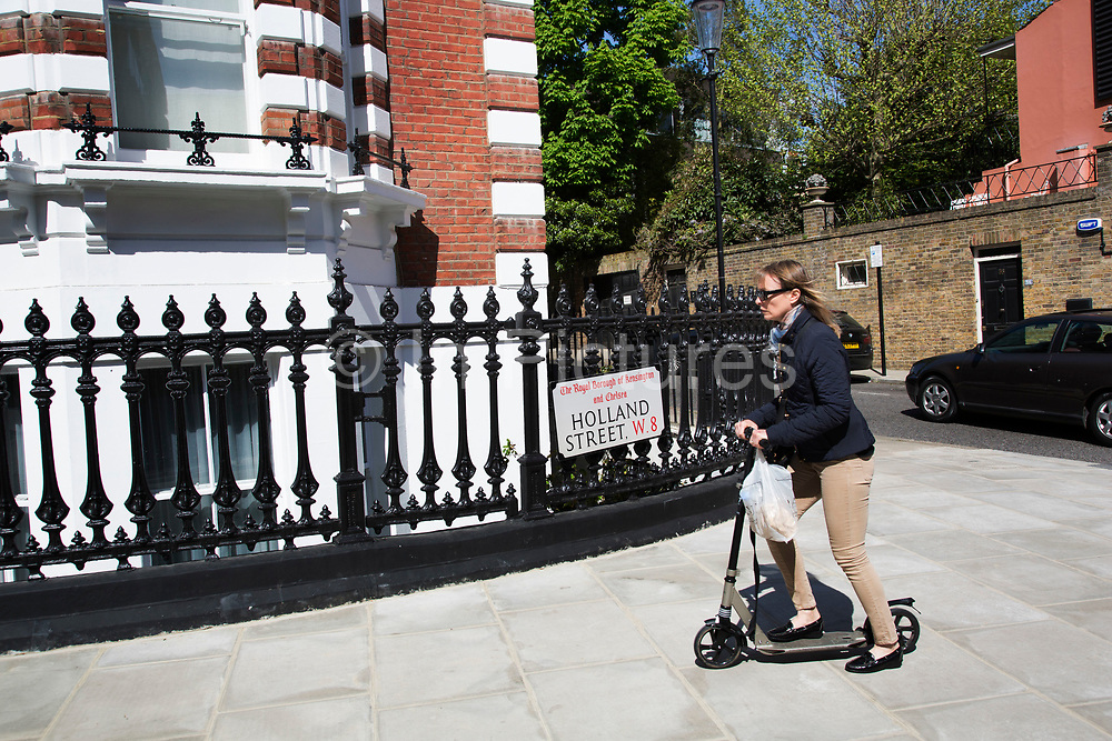 Woman scooters along the pavement on Holland Street in residential Kensington. In a selected few boroughs of West London, wealth has changed over the last couple of decades. Traditionally wealthy parts of town, have developed into new affluent playgrounds of the super rich. With influxes of foreign money in particular from the Middle-East. The UK capital is home to more multimillionaires than any other city in the world according to recent figures. Boasting a staggering 4,224 'ultra-high net worth' residents - people with a net worth of more than $30million, or £19.2million.. London, England, UK.