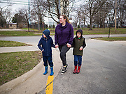 """26 MARCH 2020 - DES MOINES, IOWA: A mother and her children wait for hot meals at Weeks Middle School. Des Moines Public Schools (DMPS) started distributing hot lunches Thursday, the first day students were supposed to return to school. Schools will now remain closed until 13 April. Meals were distributed with """"social distancing"""" in mind. On Thursday morning, 24 March, Iowa reported 175 confirmed cases of the Coronavirus (SARS-CoV-2) and COVID-19. Restaurants, bars, movie theaters, places that draw crowds are closed until 07 April. The Governor has not ordered """"shelter in place""""  but several Mayors, including the Mayor of Des Moines, have asked residents to stay in their homes for all but the essential needs. People are being encouraged to practice """"social distancing"""" and many businesses are requiring or encouraging employees to telecommute.         PHOTO BY JACK KURTZ"""