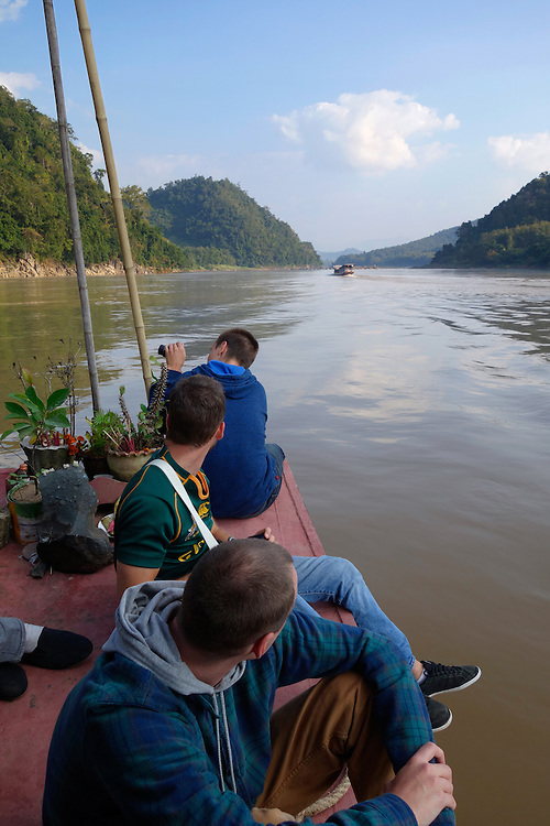 """Passengers on the bow of a """"slow boat"""" on the Mekong River in Laos."""