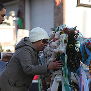 Zulma Sein, with her grand son Kevin Marc, 19, cries as she pays her respects to the shrine created under the school sign in Sandy Hook after yesterday's shootings at Sandy Hook Elementary School, Newtown, Connecticut, USA. 15th December 2012. Photo Tim Clayton
