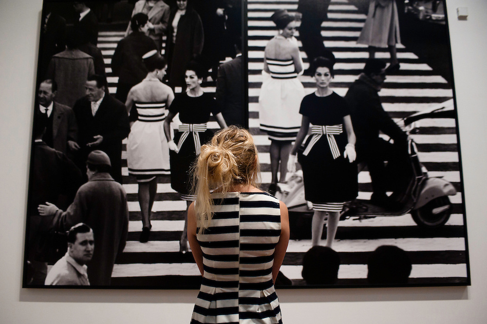 London, UK - 8 October 2012: a visitor looks up at 'Piazza di Spagna, Rome 1960' by William Klein. The exhibition examine the relationship between the work of William Klein (b.1928) and that of Daido Moriyama (b.1938). Taking as its central theme the cities of New York and Tokyo, the show explores both artists' celebrated depictions of modern urban life.