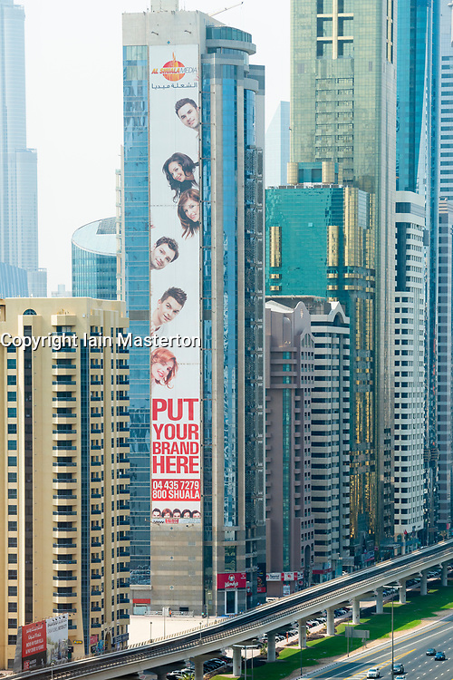 View of large advertising billboard on side of apartment tower on Sheikh Zayed Road in Dubai, UAE