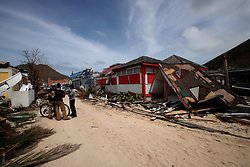Residents stand in front of the houses destroyed by Irma during the visit of France's President Emmanuel Macron in the French Caribbean islands of St. Martin, Tuesday, Sept. 12, 2017. Macron is in the French-Dutch island of St. Martin, where 10 people were killed on the French side and four on the Dutch. Photo by Christophe Ena/Pool/ABACAPRESS.COM