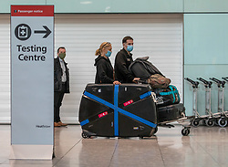 """© Licensed to London News Pictures. 24/11/2020. London, UK. Passengers walks past a Covid testing centre sign at London Heathrow Terminal 5 today. Minister for Transport Grant Shapps has announced that quarantine for air travellers will drop to 5 days from mid December if they take a private Covid test. Under the new """"test to release"""" scheme passengers who test negative after 5 days self-isolation will be able to carry on with their normal lives. Photo credit: Alex Lentati/LNP"""