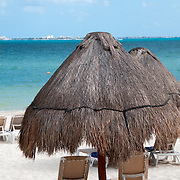 Shaded beach chairs on the white sandy beache at Excellence Playa Mujeres Resort at Playa Mujeres, north of Cancun, Quintana Roo, Mexico