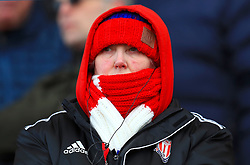 A Stoke City fan keeps warm in the stands ahead of the Premier League match at the bet365 Stadium, Stoke.