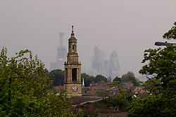 © licensed to London News Pictures. London, UK 26/04/2011. The City of London as viewed from West Norwood, South London, with St Luke's Church in the foreground. Smog clouds over the city centre following several days of hot weather. Photo credit should read Joel Goodman/LNP