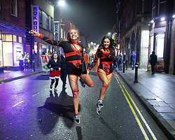 © Licensed to London News Pictures . 26/12/2018. Wigan, UK. Two women arrive and skip down King Street . Revellers in Wigan enjoy Boxing Day drinks and clubbing in Wigan Wallgate . In recent years a tradition has been established in which people go out wearing fancy-dress costumes on Boxing Day night . Photo credit: Joel Goodman/LNP