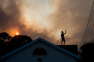 Xavier Mascareñas/Treasure Coast Newspapers; Joe Blair stands on his brother's roof on the 2900 block of Southeast Bella Road and records the scene of a wildfire that caused several evacuations Thursday, March 29, 2018, in Port St. Lucie.