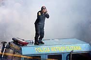 Un miembro de la Policía Metropolitana, se protege de las bombas lacrimógenas, durante una marcha realizada por estudiantes venezolanos en Caracas hoy, 1 de noviembre de 2007, en rechazo al proyecto de reforma constitucional impulsado por el presidente venezolano, Hugo Chávez para diciembre próximo. Las diferentes marchas llegaron hasta la sede del Poder Electoral. (ivan gonzalez)..