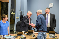 Laconia Daily Sun reporter Michael Kitch shakes hands with Laconia city councilor David Bownes as councilor Henry Lipman, right and Ava Doyle, left look on following the presentation of a proclamation by Mayor Ed Engler recognizing Kitch's 14 years of covering the council on Monday, April 24, 2017.  (Alan MacRae for the Laconia Daily Sun)