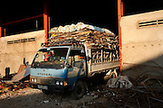 A small truck arrives with cardboard for a recycling warehouse, which operates big distribution for cardboard and paper, on the edge of Phnom Penh. The small warehouses and street side recyclers bring their cardboard and paper here in small loads. The cardboard is packed tightly into large bundles and then exported to Thailand and Vietnam. Though there are some factoryies which recycle cardboard inside Cambodia.