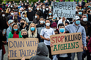 """People take part in a demonstration in front the Reichstag  building, seat of the German lower house of Parliament, the Bundestag in Berlin, Germany, August 17, 2021. About 1000 people gathered in front of the  under the call """"Airlift now! Create safe escape routes from Afghanistan!"""", the spontaneous event was organized by Seebrücke and several other human-rights organizations."""