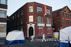 © Licensed to London News Pictures . 04/01/2015 . Manchester , UK . Crime Scene Investigators working in front of R Base nightclub on Charles Street , central Manchester , where a 26-year-old man was found fatally stabbed in the early hours of this morning (4th January 2014) . Police report being called to the scene by an ambulance crew , where they found a crowd of people on the street following a fight that spilled from a nearby club on to the street . Photo credit : Joel Goodman/LNP